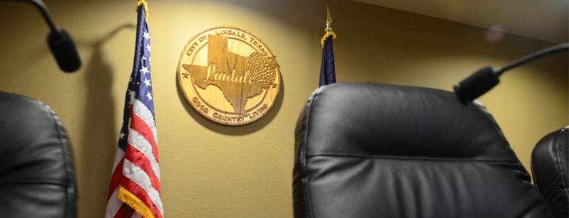 Chair in board room next to American flag and Texas plaque on wall